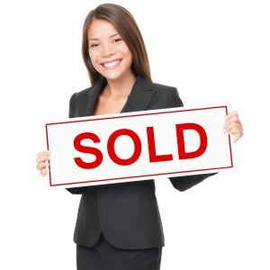 Real estate agent holding sold sign isolated on white background